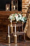 Manhã nupcial: velas ardentes em garrafa-castiçal e um arranjo com flores frescas em um vaso fotos de stock