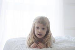 Manhã que desperta a menina da criança pequena na cama Imagens de Stock