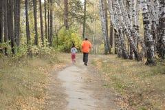 Manhã que movimenta-se com uma criança na floresta do outono fotos de stock