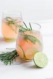 Manhã saudável com bebida, cal e alecrins frescos no fundo branco da tabela fotos de stock royalty free