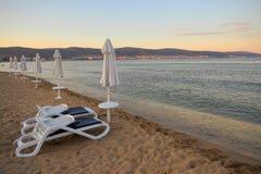 Manhã, sunbeds e parasóis na praia, fotografia de stock