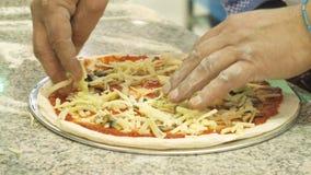 Manhänder lägger ut grönsaker och ost på pizza som är handgjord stock video