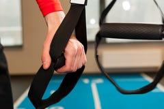 Manhänder med konditionremmar i idrottshall Arkivfoton