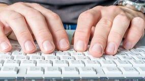 Manhänder skriver på datortangentbordet arkivfoto
