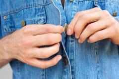 Manhänder som knäpper upp den blåa skjortan för grov bomullstvill arkivbilder