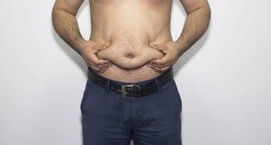 Manhänder som rymmer buken fet För showbuk för ung man fett royaltyfria foton
