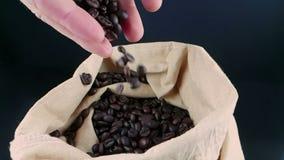 Manhänder som rymmer kaffebönor i kanfassäck och någon som ner faller, skottultrarapid på mörk bakgrund stock video