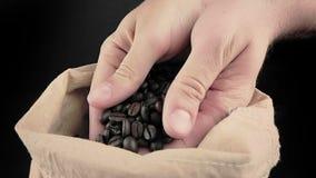 Manhänder som rymmer kaffebönor i kanfassäck och någon som ner faller, skottultrarapid på svart bakgrund lager videofilmer