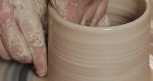 Manhänder som skapar kruset eller vasen av vit lera Vridet hjul för keramiker` s Handgjort hantverk arkivfilmer