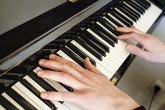 Manhänder som spelar det stora pianot royaltyfri foto