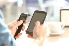 Manhänder som synkroniserar en smartwatch och en telefon fotografering för bildbyråer