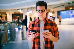 Manhåll smartphonen på shoppinggalleriabakgrund Arkivbilder