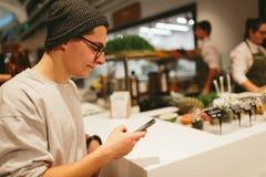 Manhåll smartphonen på shoppinggalleriabakgrund Royaltyfri Bild