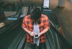 Manhåll smartphonen på shoppinggalleriabakgrund Arkivfoton