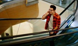 Manhåll smartphonen på shoppinggalleriabakgrund Royaltyfri Foto