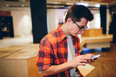Manhåll smartphonen på shoppinggalleriabakgrund Arkivfoto