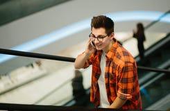 Manhåll smartphonen på shoppinggalleriabakgrund Fotografering för Bildbyråer