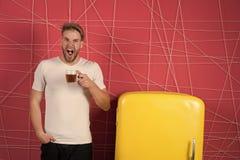Manhållkopp te eller kaffe i kök Sömnig macho gäspning på den retro kylen Ungkarl med morgondrinken på kylskåpet arkivfoton