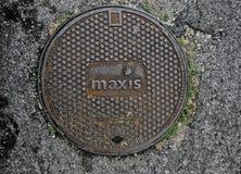 Manhålräkning som tillhör Maxis Berhad Royaltyfri Bild