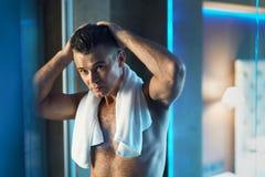 Manhåromsorg Man som trycker på hans hår i badrum Ansa för män arkivbild