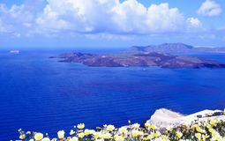 Manh? ensolarada do ver?o na ilha de Santorini, Gr?cia Mar azul, c?u azul com as nuvens na perspectiva da ilha imagens de stock