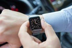 Manhand i bilen med den Apple klockan och klockan Arkivbild
