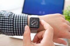 Manhand med den Apple klockan och Macbook på skrivbordet Arkivbilder