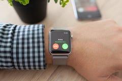 Manhand med den Apple klockan och påringningen på skärmen Arkivfoto