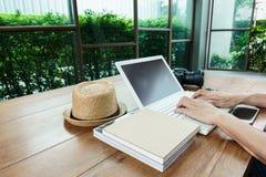 Manhand på bärbara datorn på den wood tabellen Arkivbilder