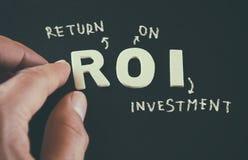 Manhand som pekar på orden ROI Return On Investment som är skriftlig på svart läderbakgrund arkivbild
