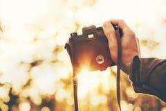Manhand som rymmer den retro fotokameran utomhus- Arkivbild