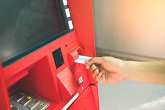 Manhand som sätter in debitering eller kreditkorten för att återta pengar med A arkivbild