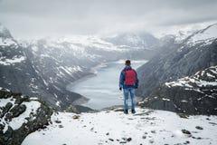 Manhandelsresande med ryggsäcken som tillbaka står på kanten och ser landskapberglandskap under snö, Trolltunga arkivfoton