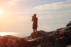 Manhandelsresandeanseende på en kulle som förbiser solnedgången med kameraloppbegrepp arkivbild