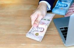 Manhanden som rymmer nya thailändska pengar 1 000 baht sedel royaltyfri foto
