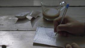 Manhandhandstil på servett och den hållande koppen kaffe i en annan hand stock video