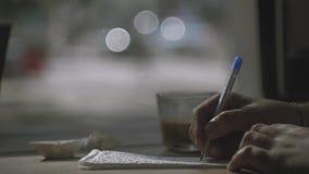 Manhandhandstil på servett och den hållande koppen kaffe i en annan hand arkivfilmer