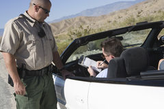 Manhandstil på biljett med trafiktjänstemannen Standing By Car Arkivbilder