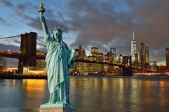 Manhattah skyline with Brooklyn Bridge at night and Statue of Li Stock Photo