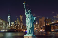 Manhattah skyline with Brooklyn Bridge at night and Statue of Li Royalty Free Stock Photos