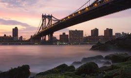 Manhattan överbryggar från Brooklyn nära solnedgång Arkivfoto