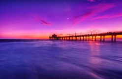 Manhattan Beach Pier. Manhattan Beach California Pier at twilight with view of Moon in the background Stock Photo