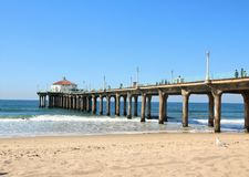 Pier at Manhattan Beach Los Angeles with a seagull. The Manhattan Beach pier juts out into the Pacific ocean on a warm February day. Surfing is popular at this Royalty Free Stock Image