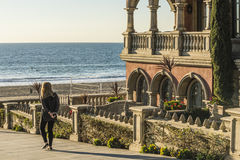 Manhattan Beach, USA - December 17, 2015: Blonde woman walking to beach boardwalk in Los Angeles area by Italian style house Stock Images