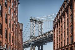 Manhattan-Brücke gesehen von den schmalen Gebäuden an einem sonnigen Tag lizenzfreies stockbild