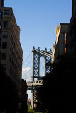 Manhattan bridge with blue sky between buildings and trees, New York Stock Photo