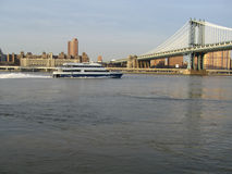 Manhattan bridge with boat. Manhattan bridge and east river nyc stock photo