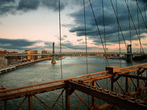 Manhattan Bridge from Brooklyn Bridge. Sun sets over East River in New York Stock Images
