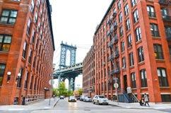 Manhattan Bridge between buildings from Brooklyn Stock Images
