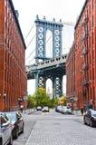 Manhattan Bridge between buildings from Brooklyn Royalty Free Stock Image